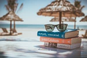 Bücher und Sonnenbrille am Strand. Babymoon, Urlaub in der Schwangerschaft | pregfit